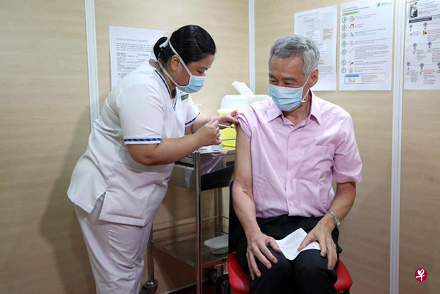​Prime Minister Lee Hsien Loong receiving his second dose of the Covid-19 vaccine at the Singapore General Hospital yesterday. It was administered by senior staff nurse Fatimah Mohd Shah, who had given him the first dose.PHOTO MCI